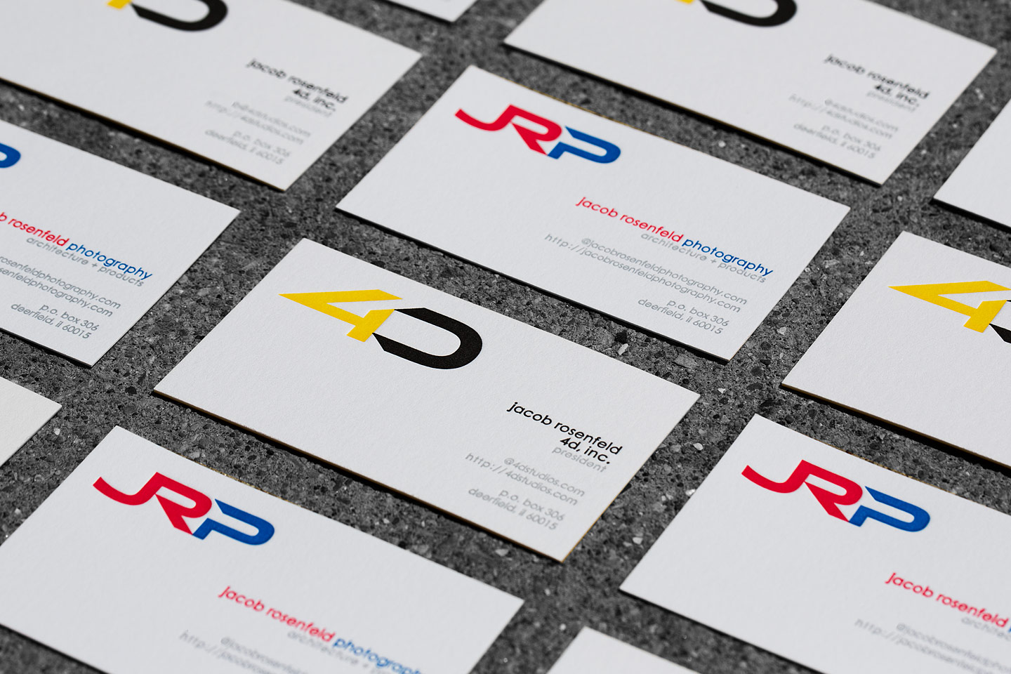 4D and JRP letterpress business cards laid out in an alternating grid