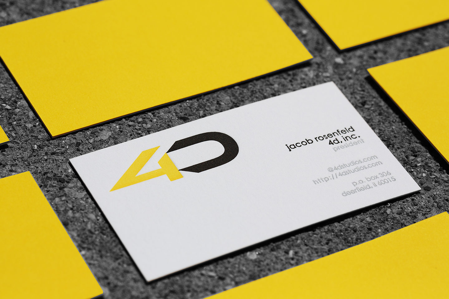 a grouping of 4D letterpress business cards, featuring one right side up with the others all upside down