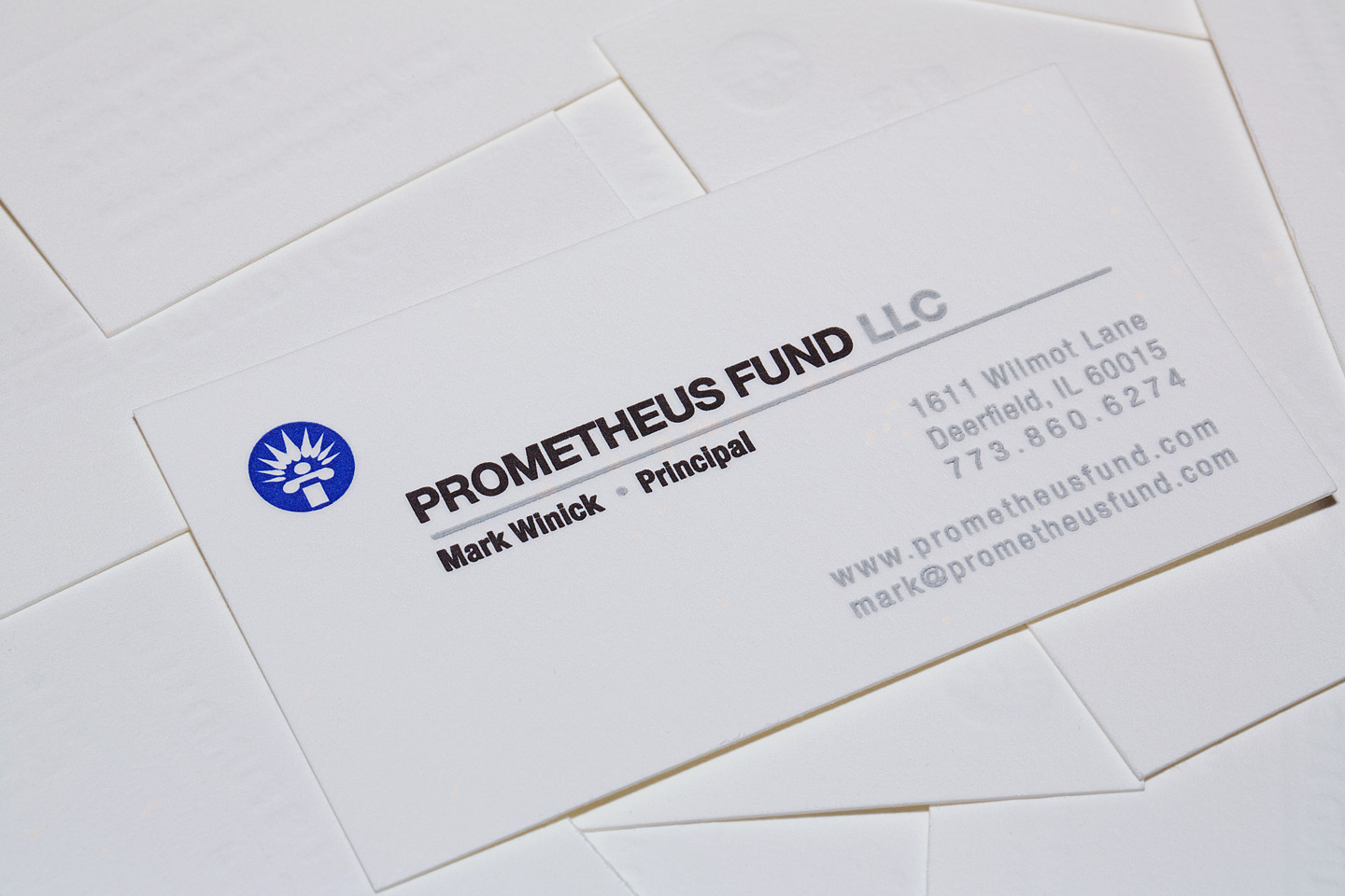 one prometheus fund llc letterpress business card sitting face-up on top of a pile of upside down business cards