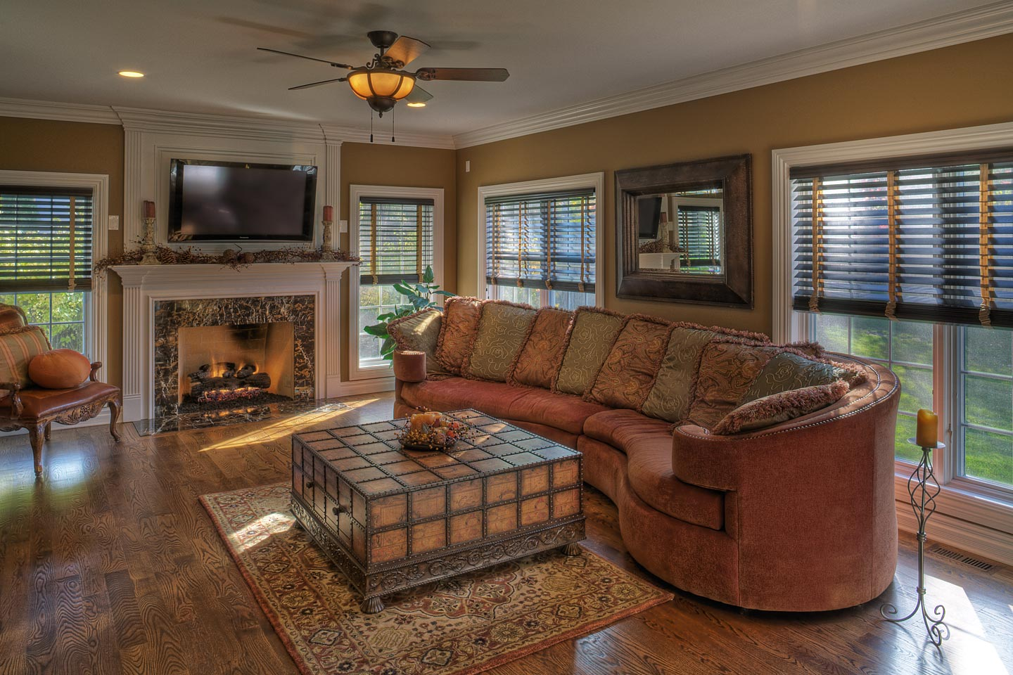 a warmly decorated family room featuring a fireplace flanked by comfortable seating, photographed by Jacob Rosenfeld