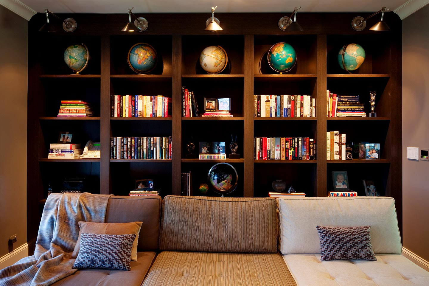 a cozy den upstairs, featuring a large built-in bookcase behind a large couch, photographed by Jacob Rosenfeld