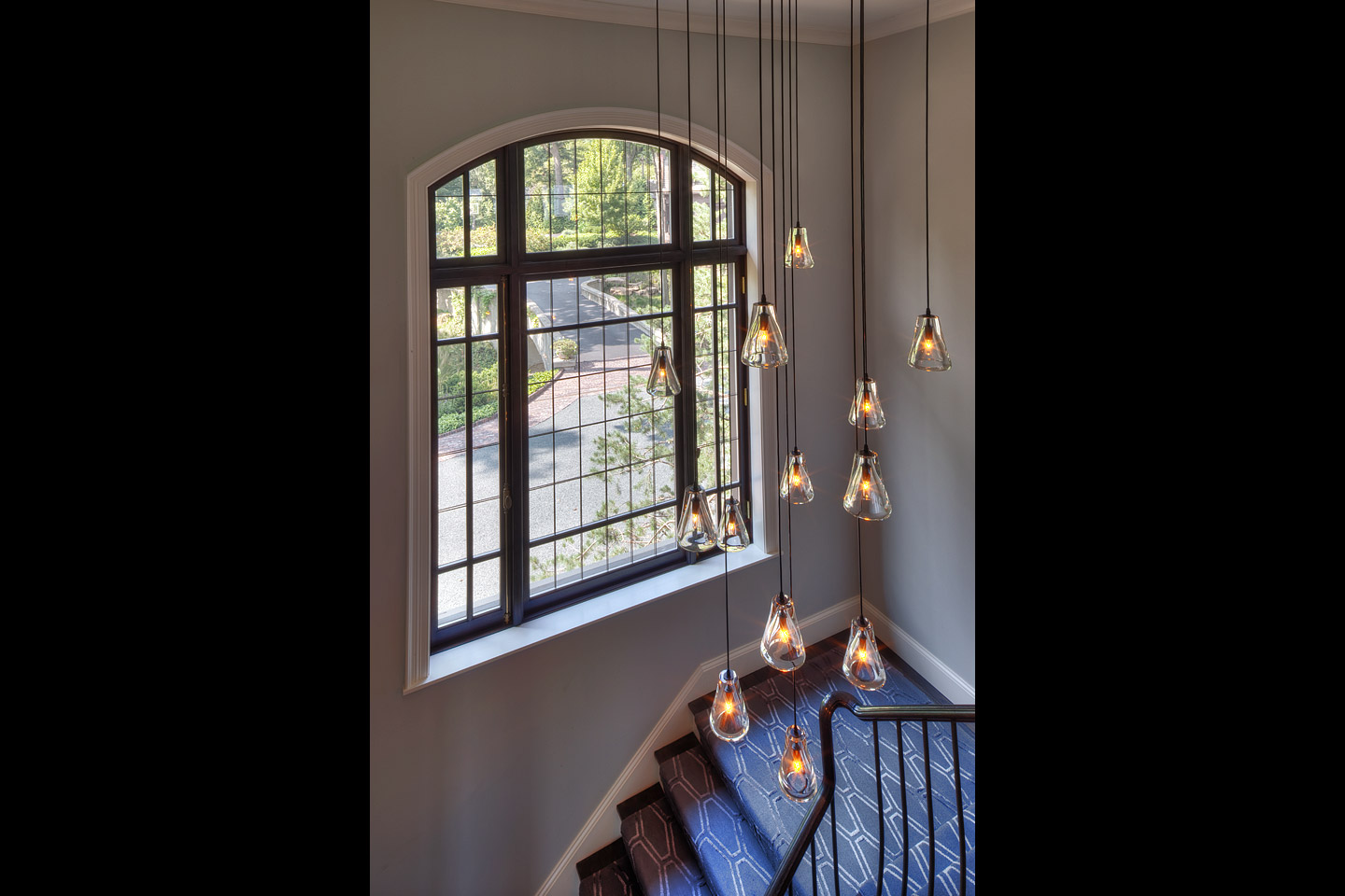 main stairwell to the second floor, featuring a hanging light fixture with beautiful blown glass shades, photographed by Jacob Rosenfeld