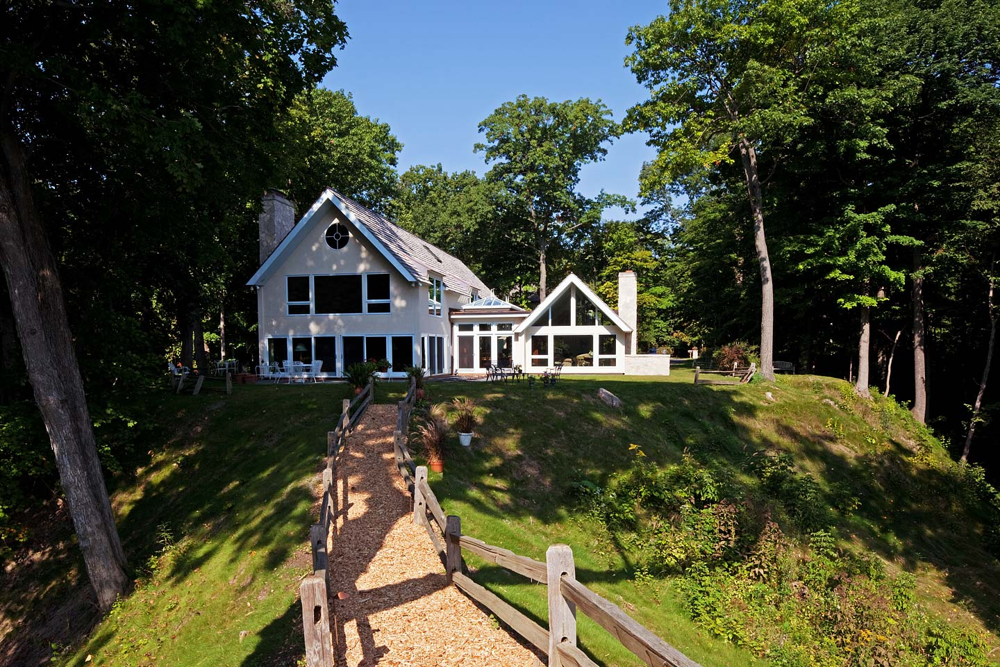 a rear exterior view of the home as seen when ascending a wood fenced path from the beach below, photographed by Jacob Rosenfeld