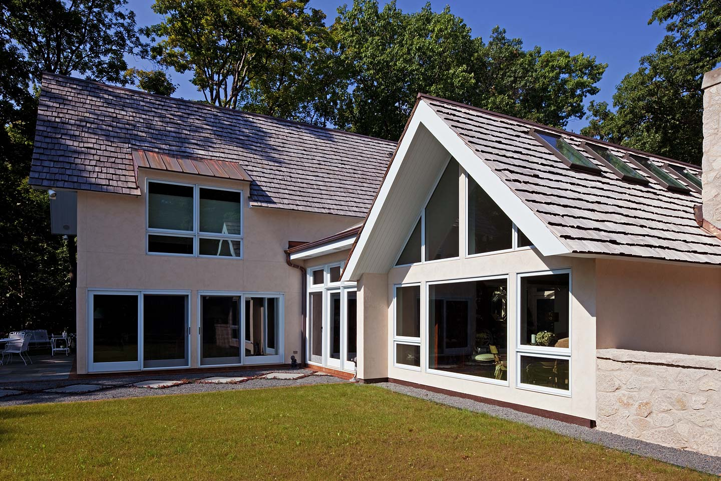 a close-up rear exterior perspective of the bungalow style home featuring a dynamic roofline, photographed by Jacob Rosenfeld