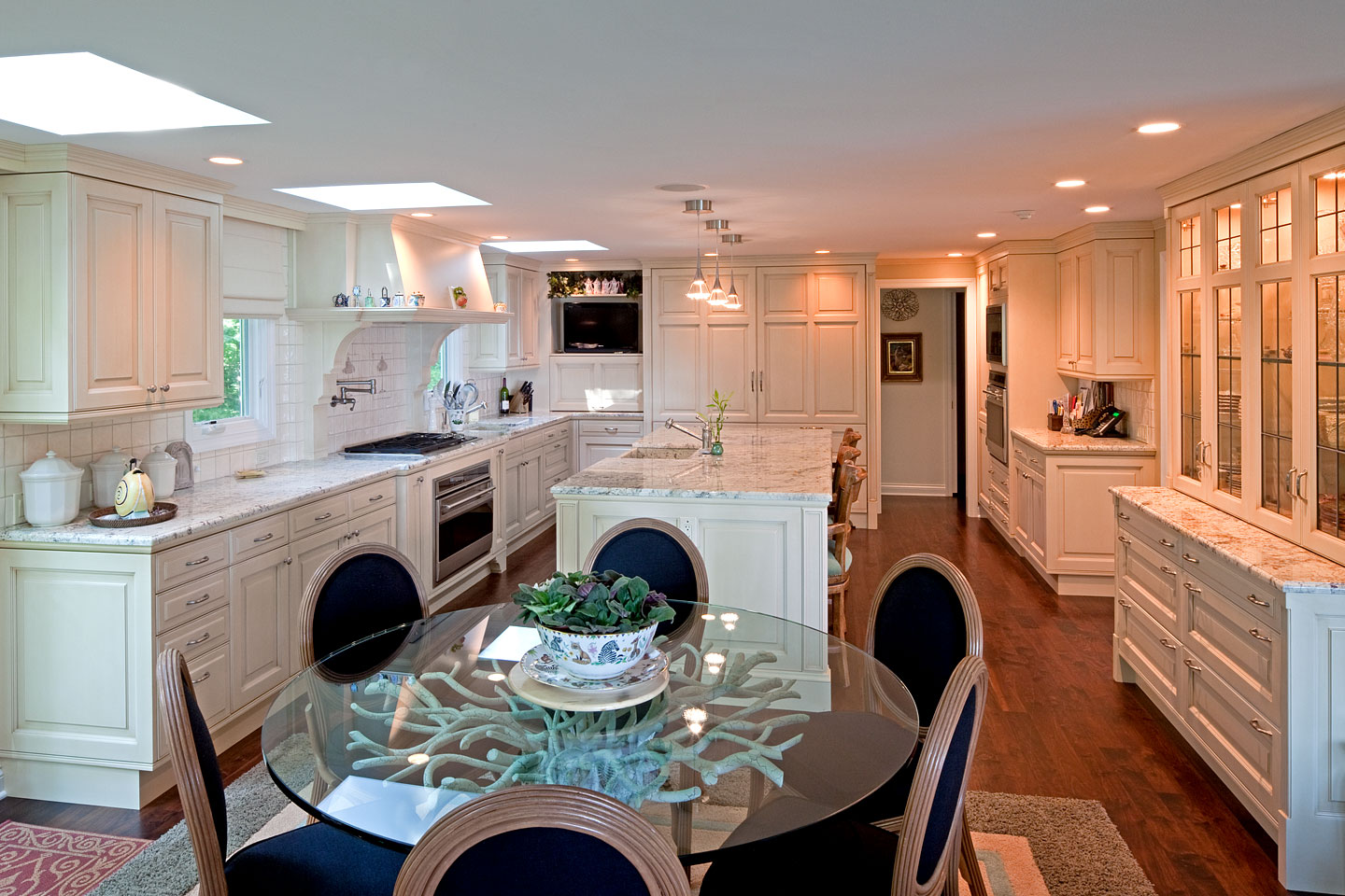 a corner perspective of a large modern kitchen, featuring high-end custom cabinetry, photographed by Jacob Rosenfeld