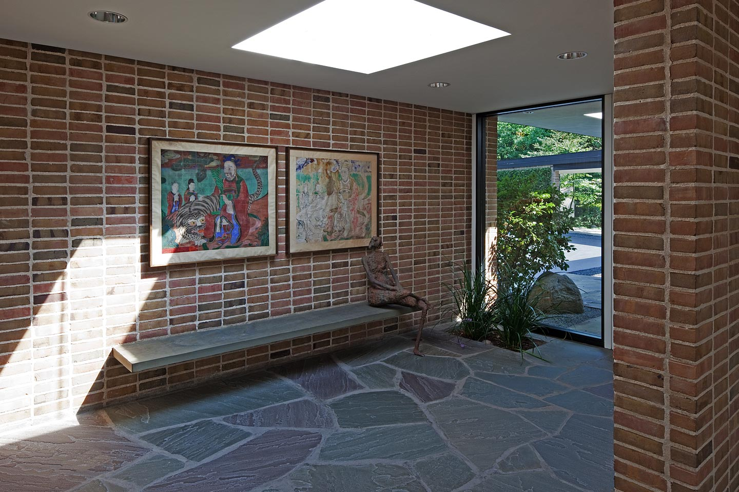 a modern brick and glass entryway, featuring green slate floors with a skylight above, photographed by Jacob Rosenfeld