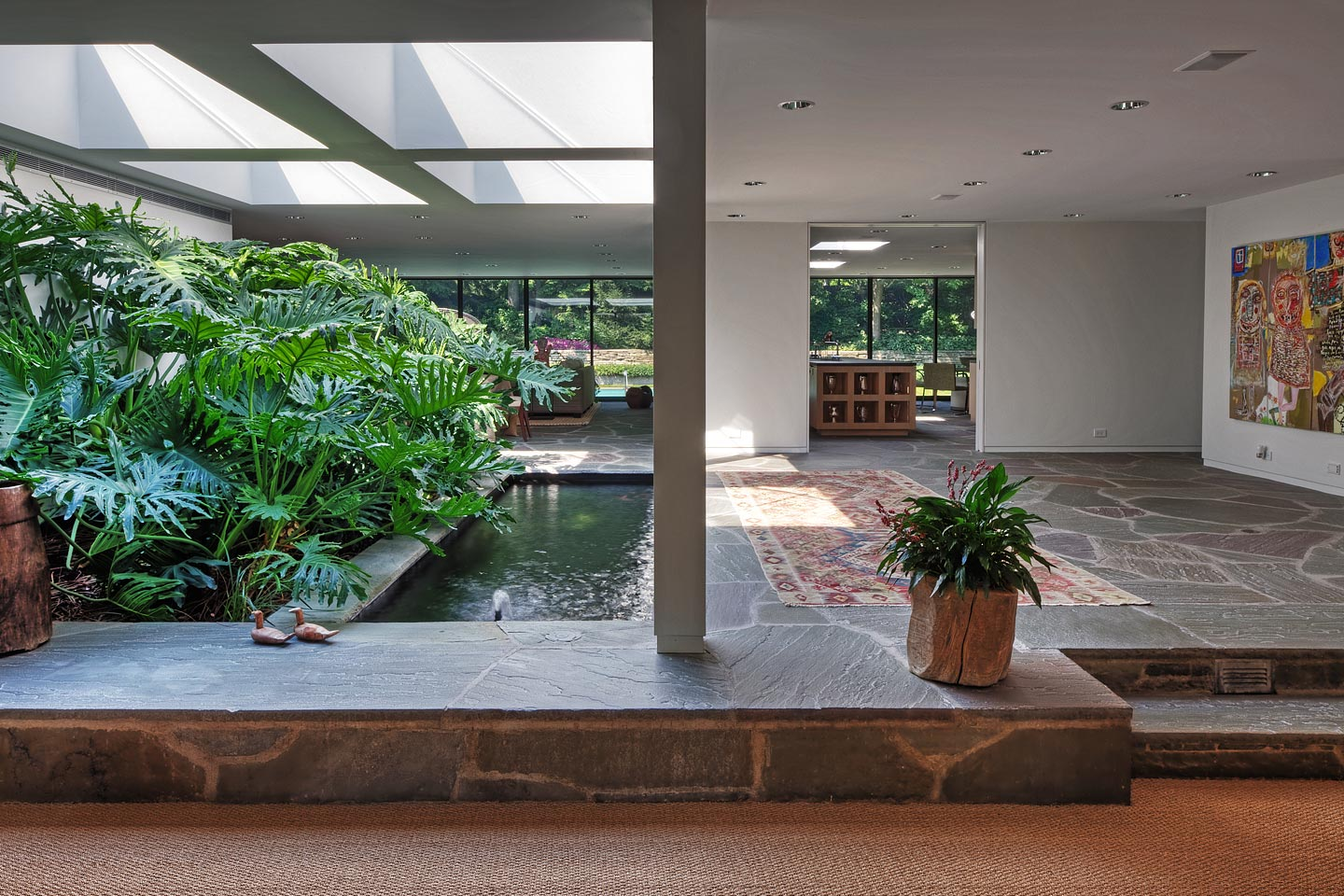 an arboretum in the foyer -- complete with a koi pond -- all lit from above via massive skylights, photographed by Jacob Rosenfeld