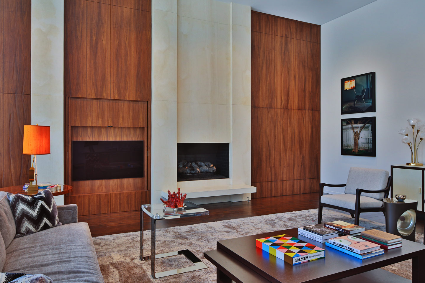 a modern great room featuring a minimal fireplace surrounded by massive wooden panels, photographed by Jacob Rosenfeld