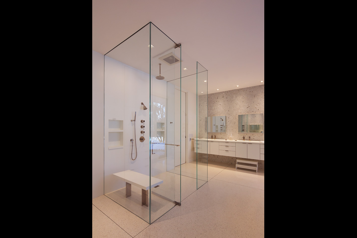 a modern master bath featuring a floor to ceiling frameless glass cube shower and floating vanities, photographed by Jacob Rosenfeld