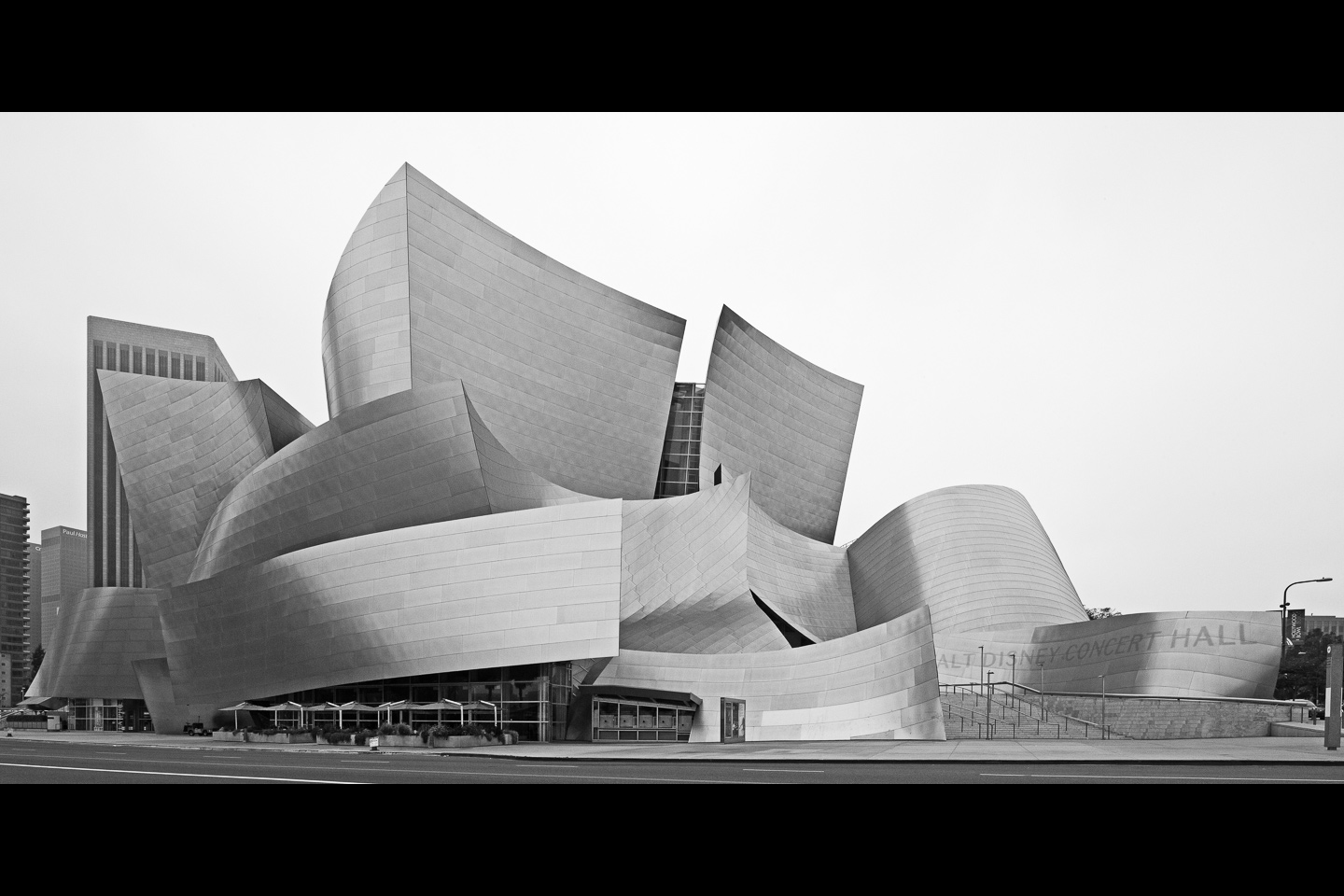 a black & white street view of the Walt Disney Concert Hall, designed by Frank Gehry, located in Los Angeles, photographed by Jacob Rosenfeld