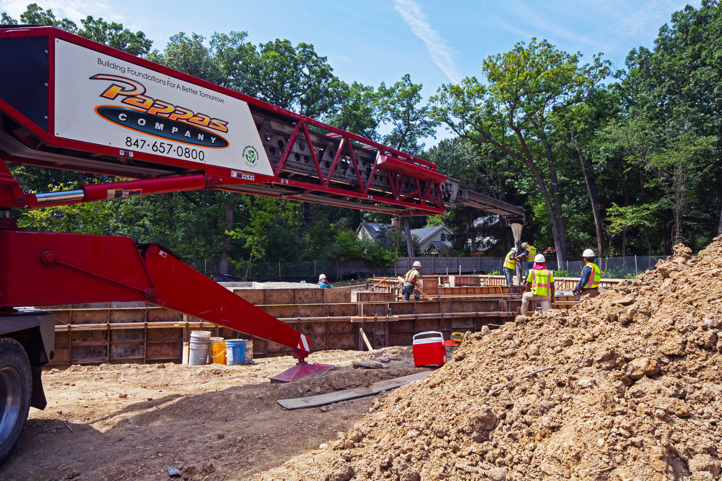 Massive concrete conveyor truck arm delivering concrete for the foundation walls