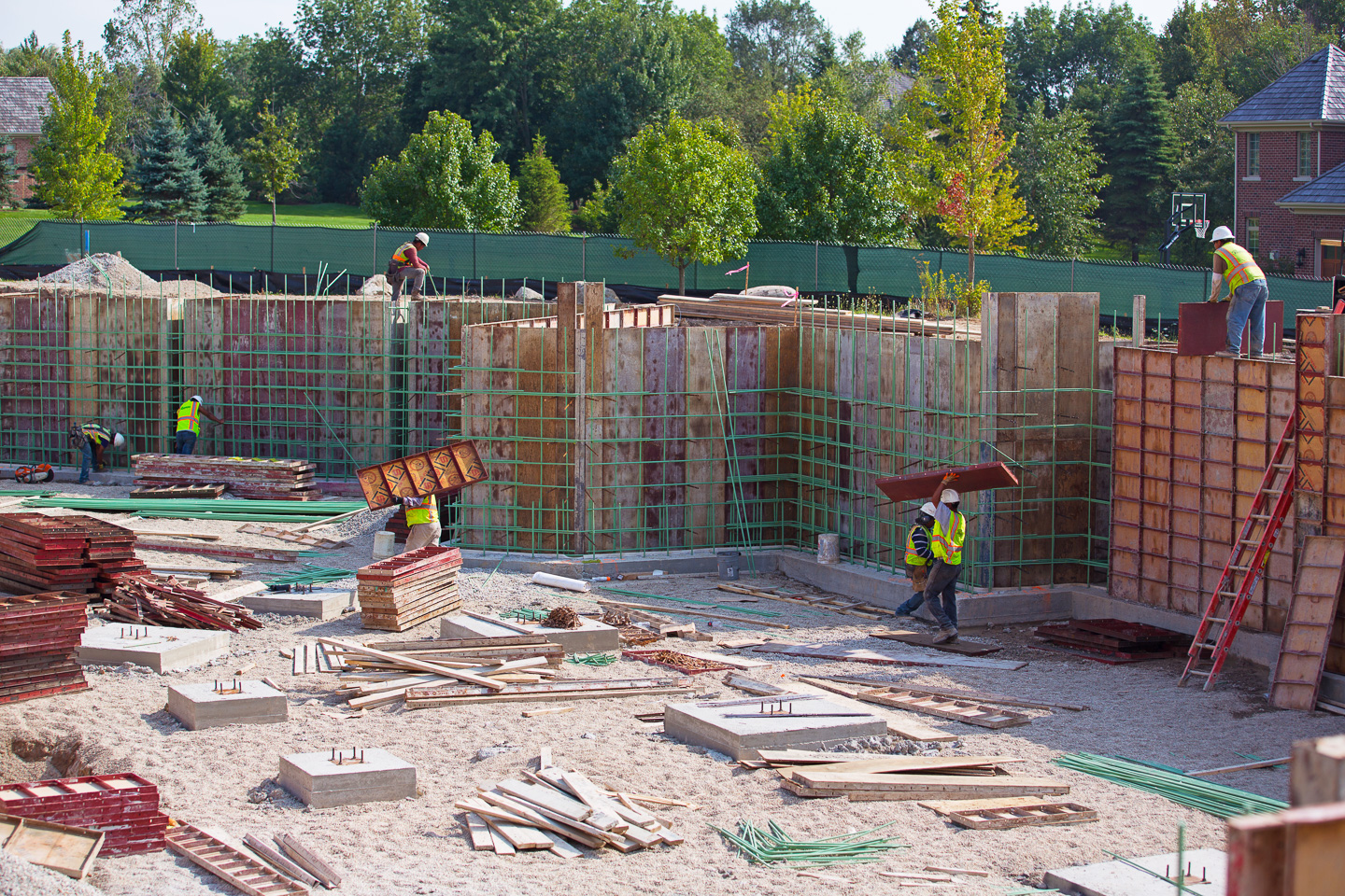 Construction workers prepping for concrete foundation wall pour.