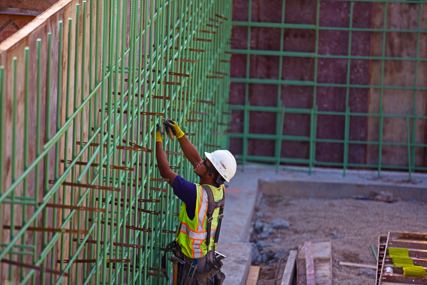 Construction worker securing rebar to steel clips