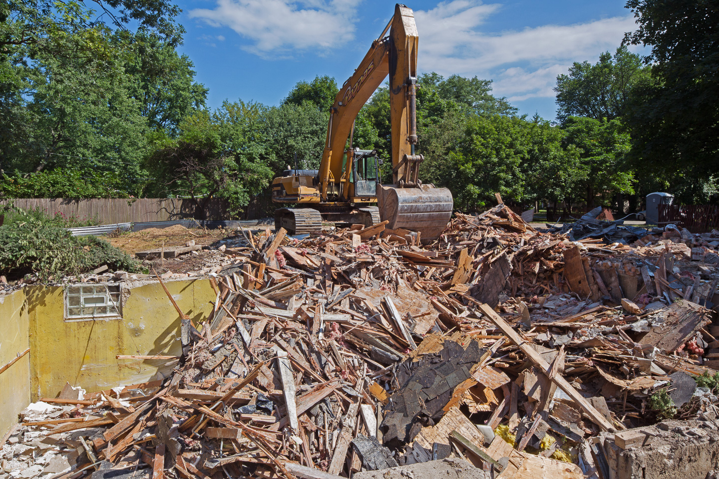 Site demolition - a picture of a backhoe destroying a home.