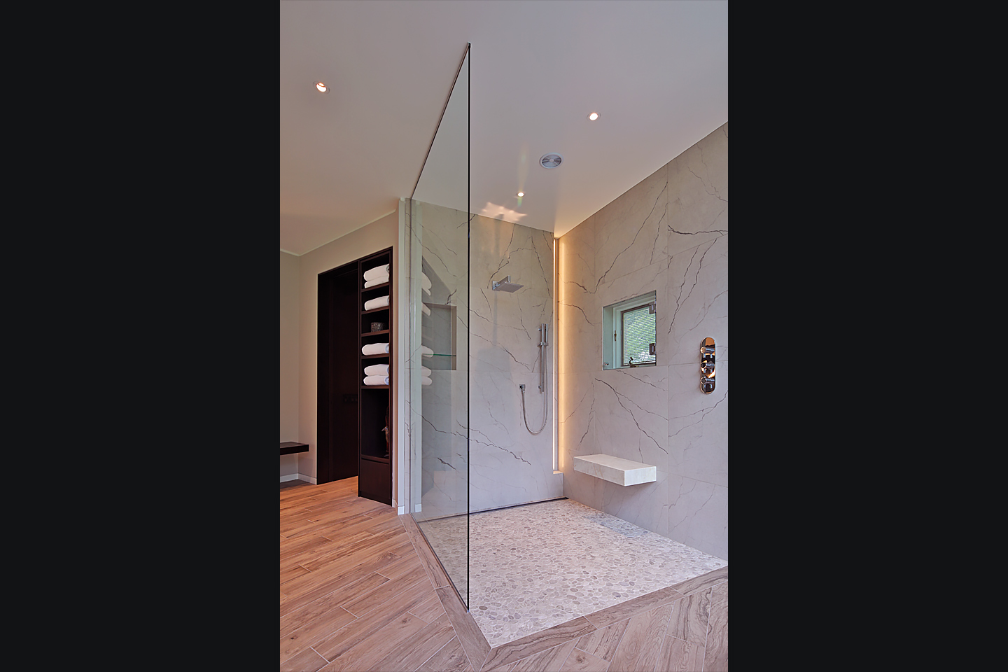A modern, open master shower framed by glass and marble, photographed by Jacob Rosenfeld